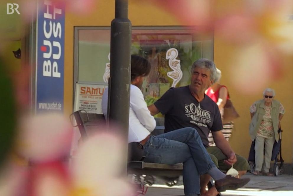 zwei Männder sitzen auf einer Bank in der Fußgängerzone