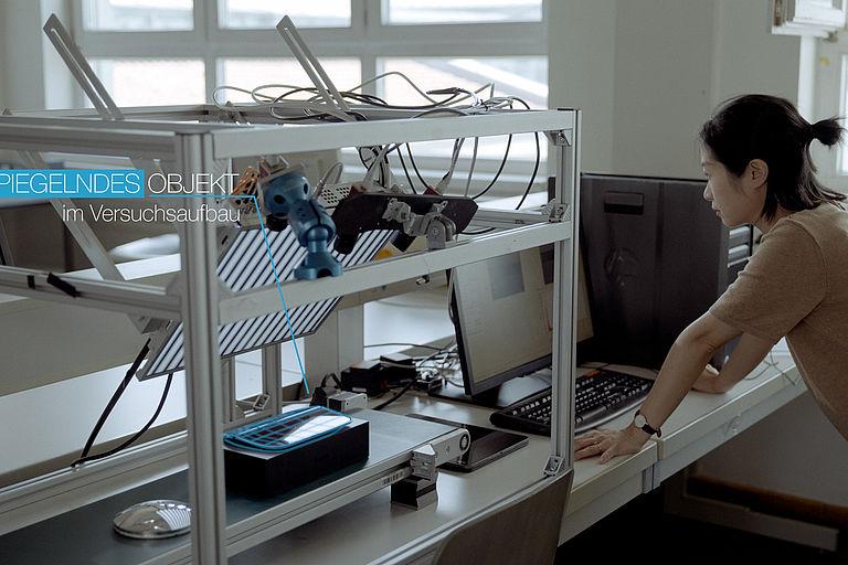 Frau steht vor einem PC - daneben ein Testaufbau