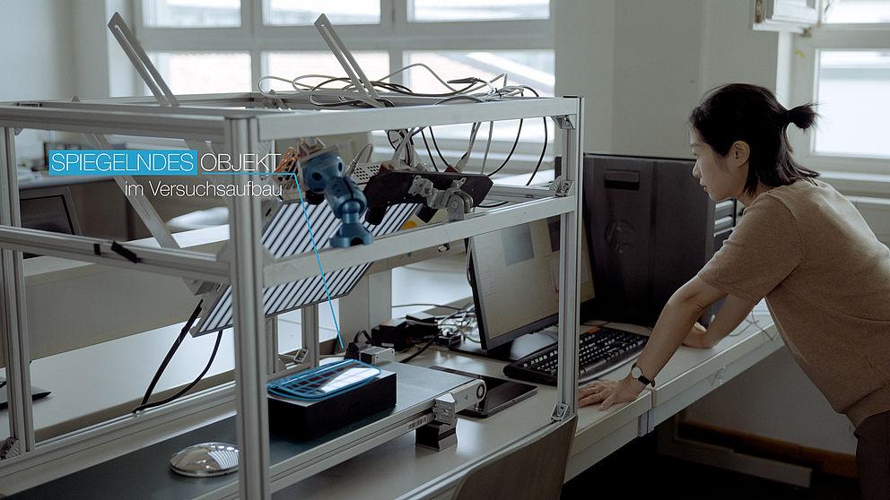 Frau steht vor einem PC - daneben Testaufbau