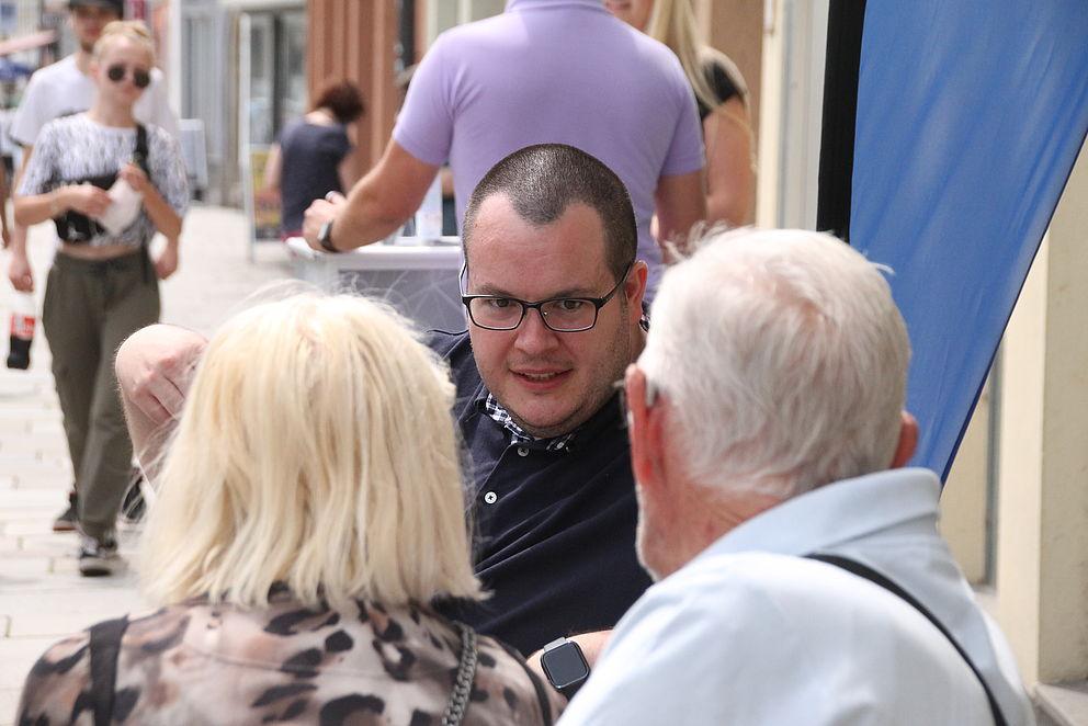 Ein Mann sitzt mit zwei anderen Menschen auf der Bank und unterhält sich