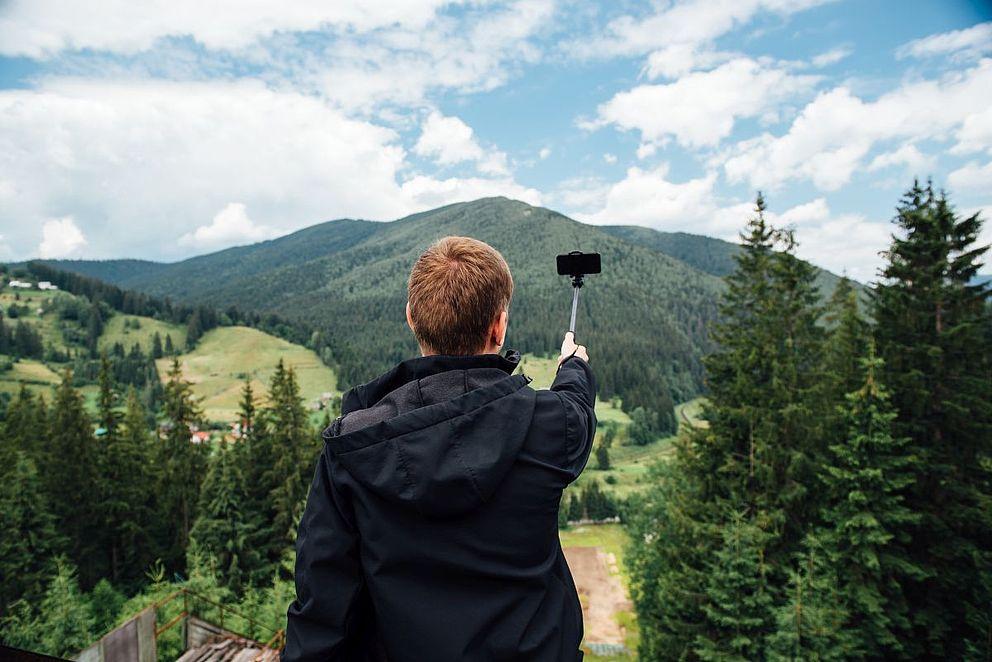 Wanderer am Berg mit Selfie Stick